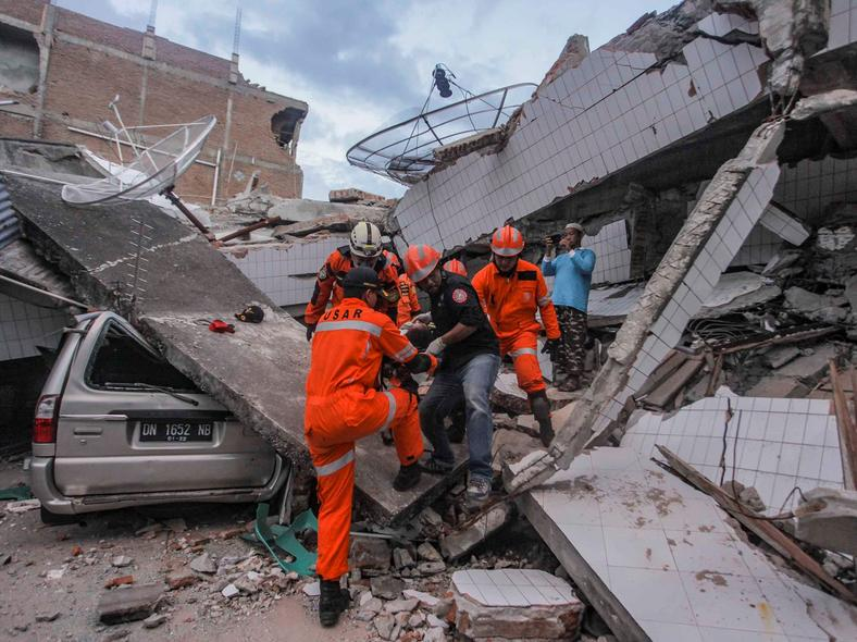 Search and rescue workers evacuate an earthquake and tsunami survivor trapped in a collapsed restaurant in Palu, Central Sulawesi, Indonesia.