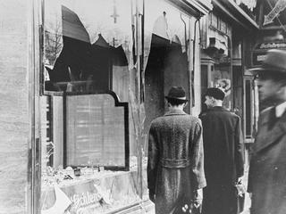 Germans pass by the smashed windows of a Jewish-owned shop. The aftermath of Kristallnacht (Night of
