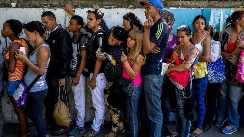 People queue to buy basic food and household items outside a supermarket in Caracas, on September 28, 2016