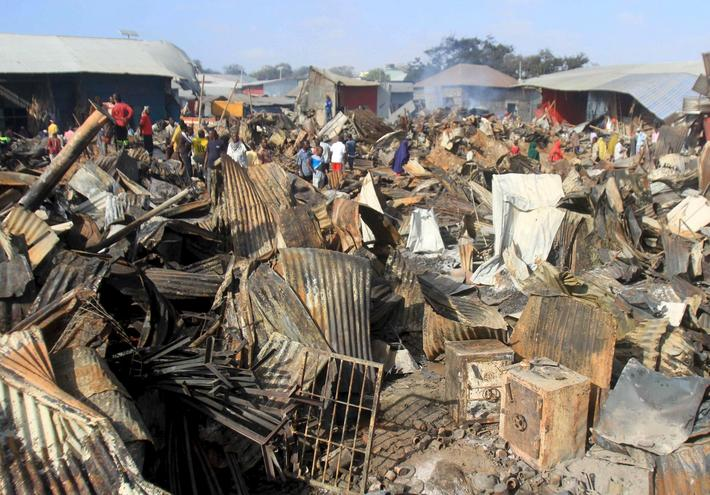 Twisted iron roofing is seen in the foreground after a night fire razed down a busy market in Mogadi