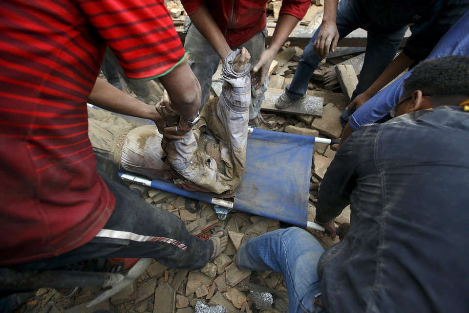 Rescue workers lift the body of a victim onto a stretcher, after an earthquake hit, in Kathmandu, Nepal