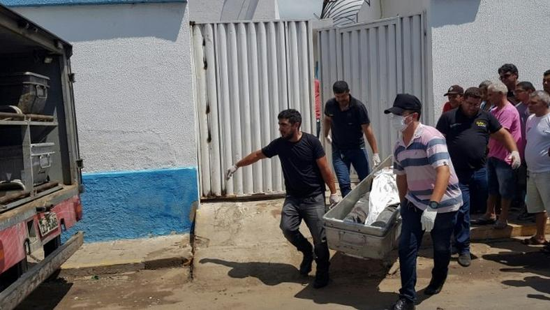 Forensic experts carry a corpse to be transported to the morgue after an attempted bank robbery in Milagres, Ceara state, Brazil