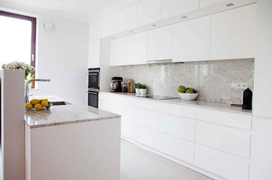 Otwarta kuchnia z szafkami o gładkich frontach zlewa się z tłem ściany, nie dominując w strefie dziennej.