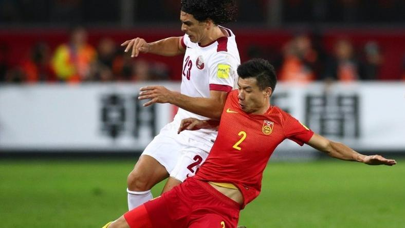 China's Mei Fang (right) competes for the ball with Qatar's Sebastian Soria during their 2018 World Cup qualifier in Kunming on November 15, 2016