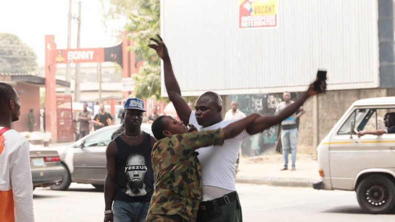 A military personnel frisks a Lagos state government official in Victoria Island on Tuesday, February 25, 2020 (Lagos state govt)