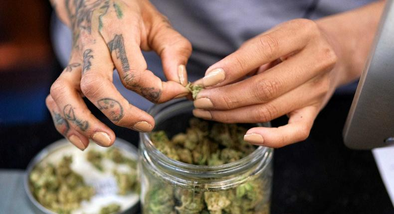 A budtender weighs out marijuana for a customers at ShowGrow, a medical marijuana dispensary in downtown Los Angeles.
