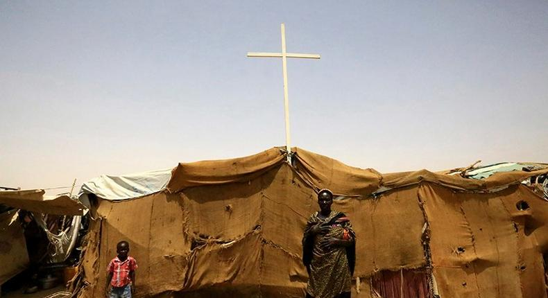 People from South Sudan stand near a tent used as a church at a railway station camp, where they have spent the last four years, in Khartoum on May 11, 2014
