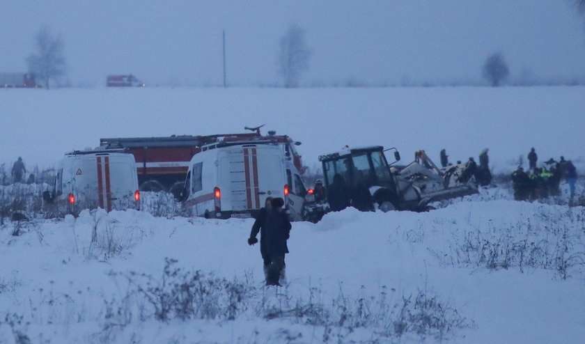 Emergency services work at the scene where a short-haul regional Antonov AN-148 plane crashed after