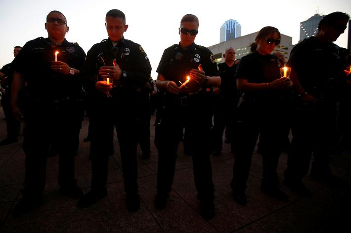 Dallas police officers take part in a candlelight vigil at Dallas City Hall
