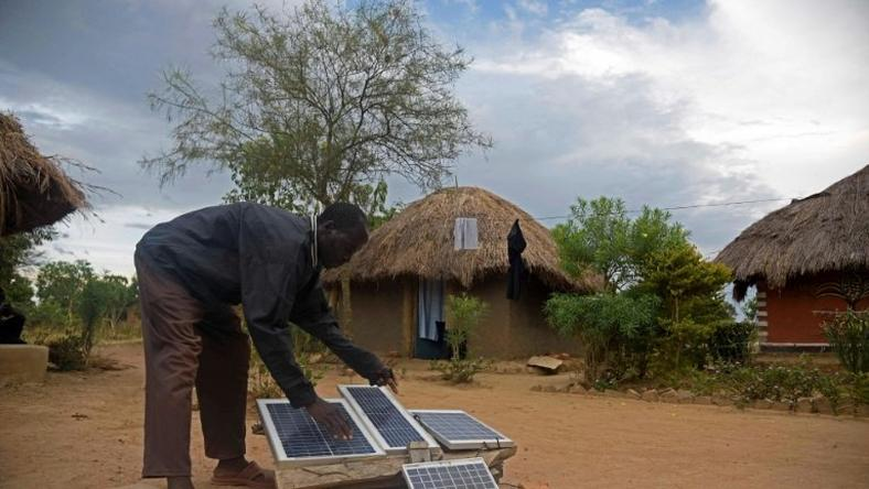 Robert Otala checks on solar panels that he uses for his home in Soroti District about 300 kilometres northeast of the capital Kampala