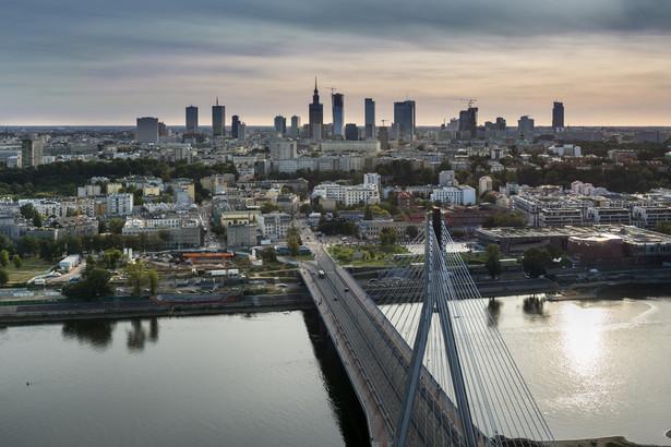 """Panorama Warszawy: na pierwszym planie Most Świętokrzyski, w tle warszawskie """"city"""" finansowe."""