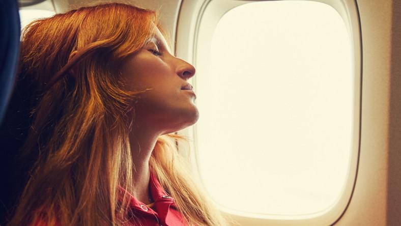 Kobieta śpi w samolocie