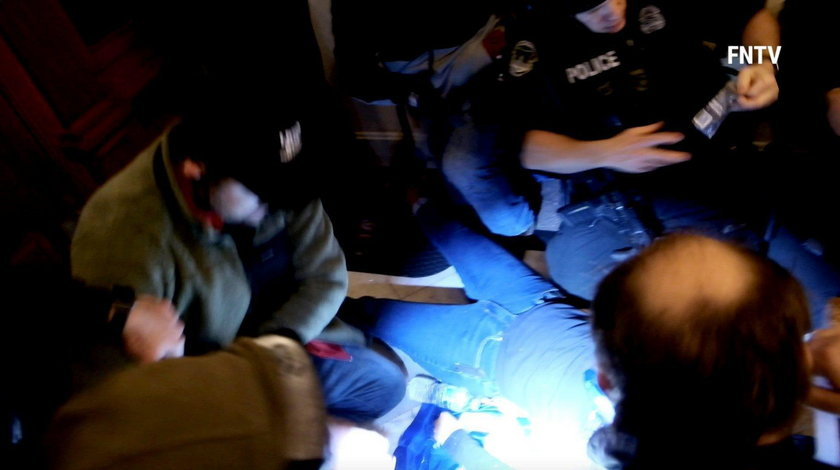 People and police help a woman, who was shot, as she lies on the floor, after supporters of U.S. Pre