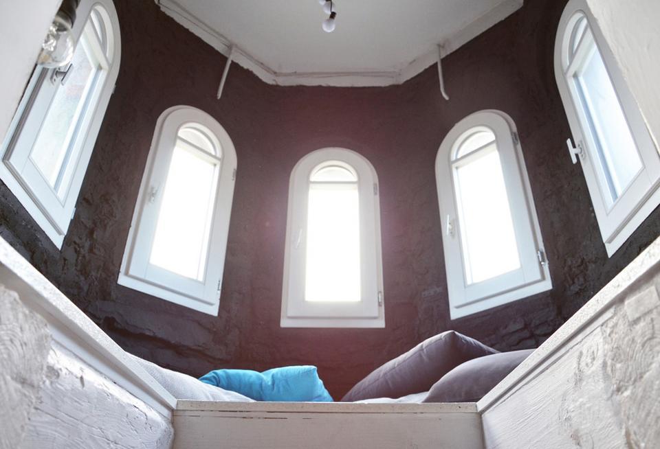 Wnętrze wieżyczki z podestem i poduchami.