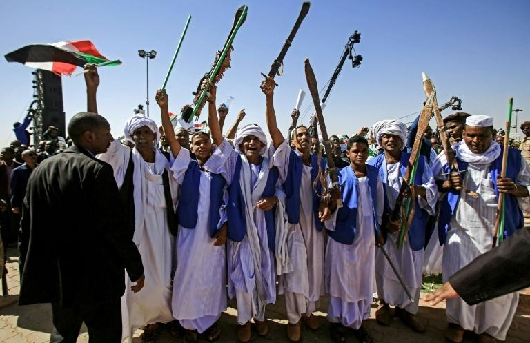 Supporters of Sudan's President Omar al-Bashir raise up sticks and swords in salute as they gather during a rally for him in the Green Square in the capital Khartoum on January 9, 2019