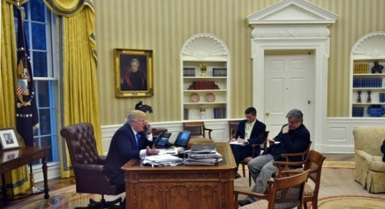 US President Donald Trump speaks on the phone with Australians Prime Minister Malcolm Turnbull, alongside Chief Strategist Steve Bannon (R) and National Security Advisor Michael Flynn, in the Oval Office on January 28, 2017