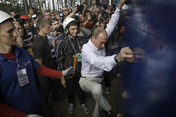 """Putin wciąz podkreśla swoją tężyznę fizyczną. Według Newsweeka, Putin, gdy nie pracuje, chętnie czyta biografie władców Rosji, Iwana Groźnego, Katarzyny II, czy Piotra Wielkiego. Jednak jego pasją jest sport. Gra w hokeja z ochroniarzami, ma czarny pas w judo, podobno był nawet mistrzem Leningradu. Siedem lat temu podzielił się swoją wiedzą z Rosjanami, wydał płytę """"Naucz się judo z Władimirem Putinem"""". Ponadto prezydent Rosji pływa, strzela, jeździ konno, jeździł bobslejami, trenował biathlon, a nawet walczył z niedźwiedziem. Lubi popisywać się swoją tężyzną fizyczną, świat obiegły jego zdjęcia z nagim torsem. Na zdjęciu – prezydent Rosji pokazuje młodzieży, jak się wspinać, podczas Międzynarodowego Forum Młodzieży """"Seliger 2011"""". Źródło: Kremlin.ru"""