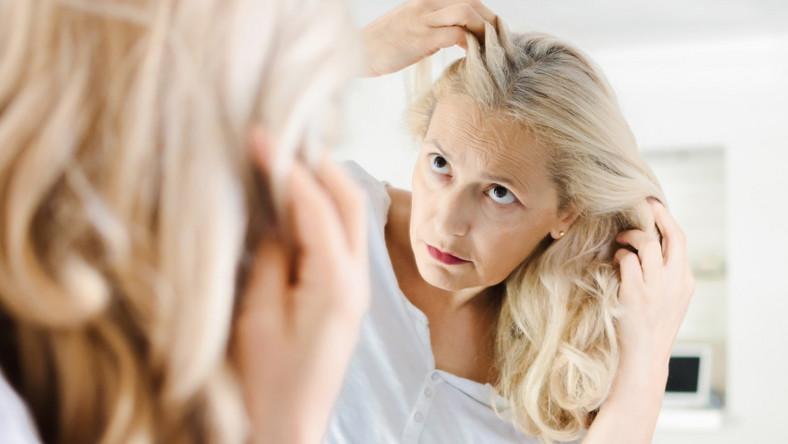 Dojrzała kobieta ogląda włosy w lustrze