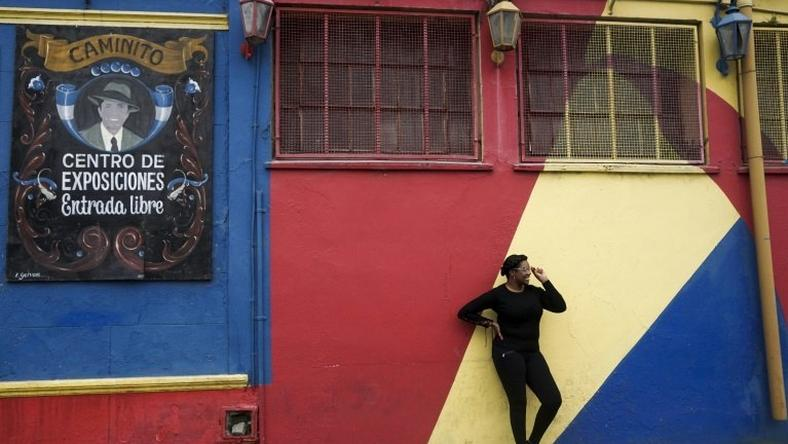 A tourist poses for pictures during a visit to the traditional street museum Caminito in La Boca neighbourhood in Buenos Aires