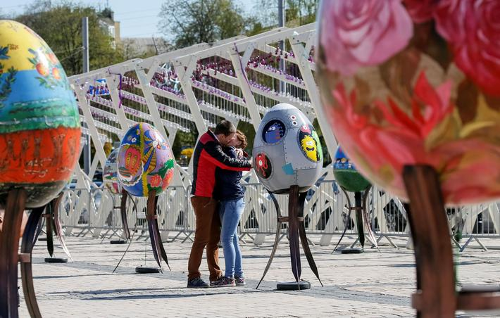 "Couple kisses near traditional Ukrainian Easter eggs ""Pysanky"", displayed at square, as part of upco"