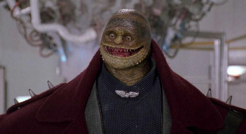 A screenshot from the 1993 Super Mario Bros. movie featuring the film's version of a Goomba villain from the game series.
