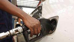 A petrol station attendant fuelling a car