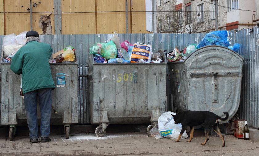 Bezdomny szuka czegoś w śmieciach