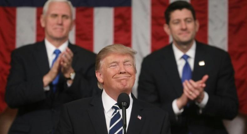 US Vice President Mike Pence (left) and House of Representatives Speaker Paul Ryan (right) applaud as President Donald Trump delivers his first address to a joint session of Congress