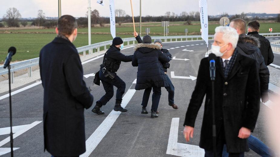 Premier Mateusz Morawiecki, a z tyłu protestujący rolnicy
