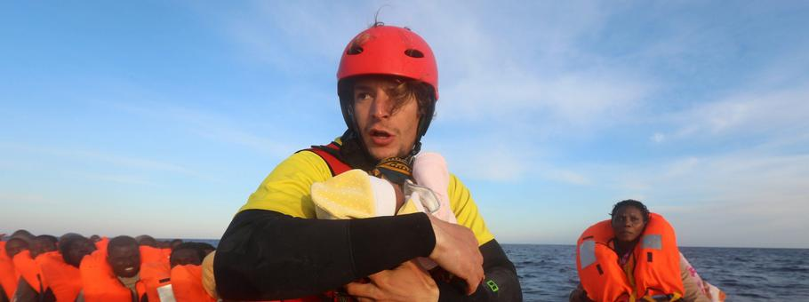 Spanish rescuer Daniel Calvelo carries a four-day-old baby girl into a RHIB, during a search and res