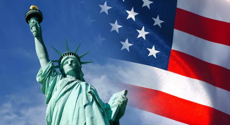 Statue of Liberty and United States flag waving in wind