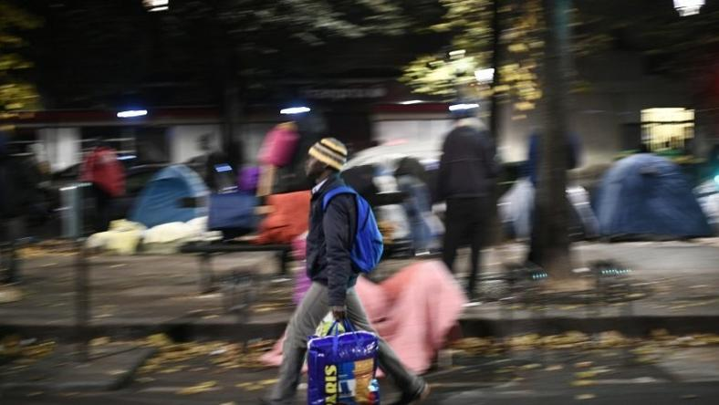 Migrants collect their belongings on the Avenue de Flandre during the evacuation of a makeshift camp in Paris on November 4, 2016