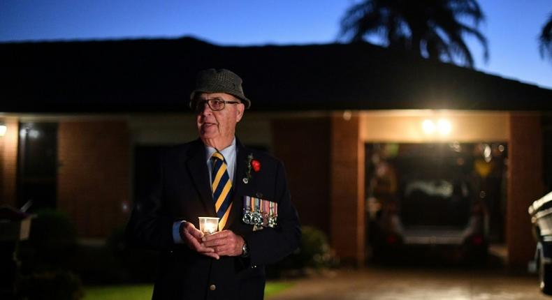 Veteran Peter McFarlane holds a candle during an Anzac Day dawn vigil outside his house in suburbs of Sydney