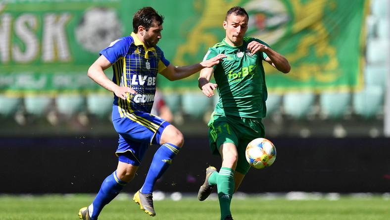 Zawodnik Śląska Wrocław Augusto (P) i Mateusz Młyński (L) z Arki Gdynia podczas meczu grupy spadkowej piłkarskiej Ekstraklasy