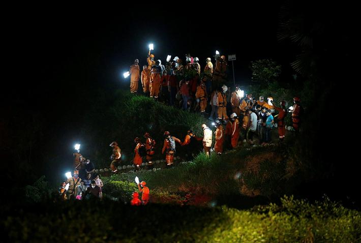 Rescue members walk during the burial of a companion who died after flooding and mudslides caused by