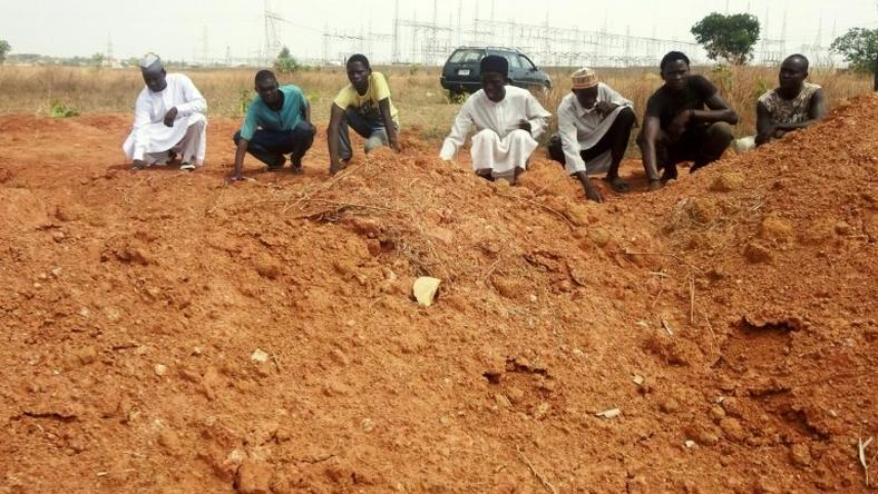 Members of the Islamic Movement of Nigeria (IMN), a Shiite group, pray at a mass grave in the outskirts of northern Nigerian city of Kaduna