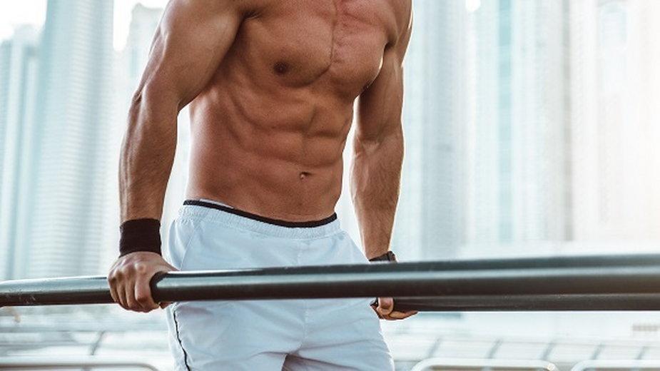 Półnagi mężczyzna robi ćwiczenia z paskami