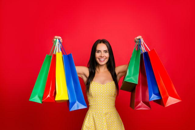 Portrait of cheerful charming well-dressed elegant glamorous with beaming toothy smile showing many colorful bags isolated on bright red background